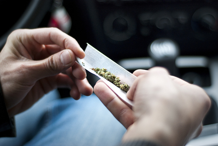 man making joint and a stash of marijuana in the car