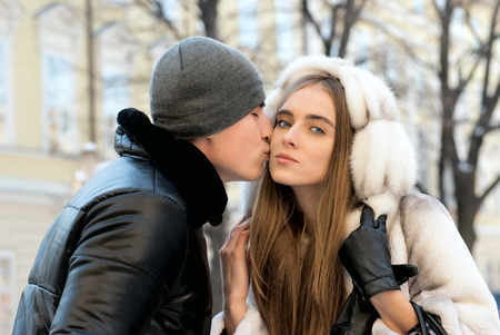 couple winter: Young couple kissing in winter outdoors portrait