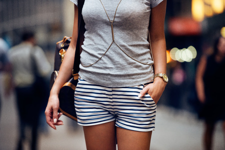 lady hand: Outfit details of fashion elegant stylish woman posing. Female summer outfit with short striped blue and white shorts, grey t-shirt, modern leather backpack and golden jewelry and watch standing on city street. Stock Photo