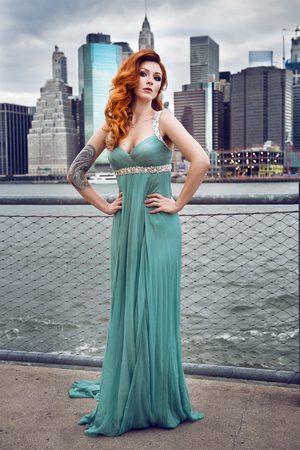 red haired woman: Beautiful red haired woman with tattoo wearing green dress posing in New York City Stock Photo