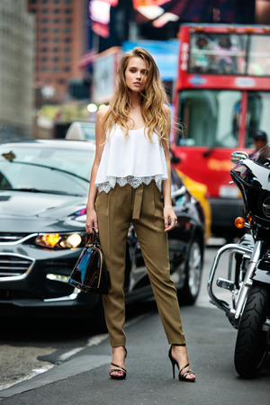 Beautiful fashionable woman standing on city street on car traffic wearing green pants, white sexy t-shirt and holding bag. Girl traveling and shopping in New York CIty at summer.