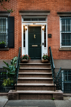 Front Door of a Beautiful Georgian Era English Manhattan Town House. New York City home building entrance with green door and steps.