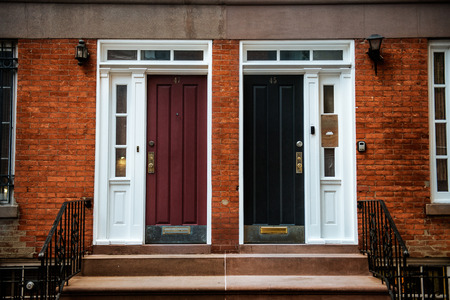 neighboring: View of Front Doors of Two Neighbouring Red Brick English Town Houses on a Residential Estate. New York City Manhattan buildings.