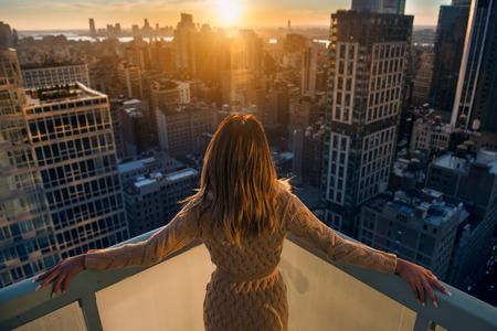 豊富な女性では、ニューヨークの高級マンションでバルコニーで夕日の立っているお楽しみください。豪華な生活の概念。成功 B 実業家でリラック