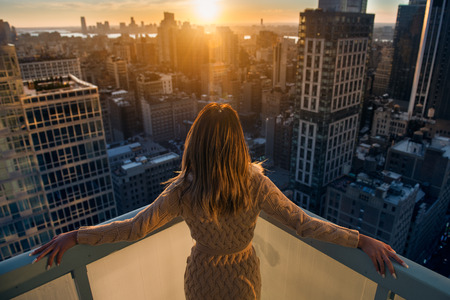 Reiche Frau genießen den Sonnenuntergang auf dem Balkon in Luxus-Apartments in New York City steht. Luxus-Leben-Konzept. Succesful B Geschäftsfrau entspannen.