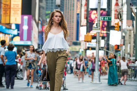 sexual activities: Attractive young adult woman walking around crownd on New York City street and carrying a bag wearing white top and pants