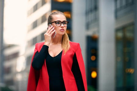 Elegant businesswoman walk in city financial district and talking on cell phone wearing jacket and eyeglasses. Succesful business woman walking near skyscrapers. Stock Photo