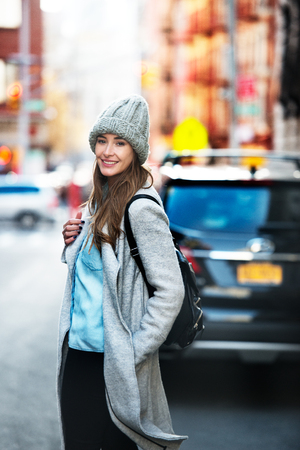 Beautiful student woman ready get in into her car capked on city street. Cute smiling woman wearing autumn casual street style outfit and backpack walking on city street. Stock Photo