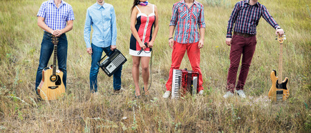 Concept photo of music band with guitars, microphone and accordion standing outdoors