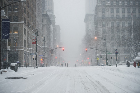 New York City Manhattan Midtown street under the snow during snow blizzard in winter. Empty 5th avenue with no traffic.
