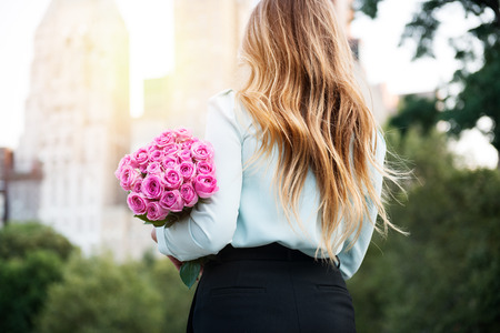Beautiful girl holding bouquet of pink roses flowers on dating in the city. Businesswoman with bunch of flowers. Veiw from the back.