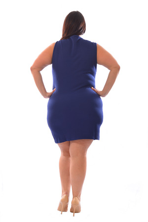 Full-body portrait of plus size model woman wearing XXL blue dress posing isolated on white background. View from the back. Stock Photo