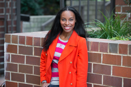 african america: Happy beautiful african america woman wearing red jacket standing and smiling at student college campus.