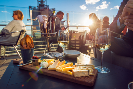 People having dinner at rooftop restaurant with wine and cheese at sunset time.