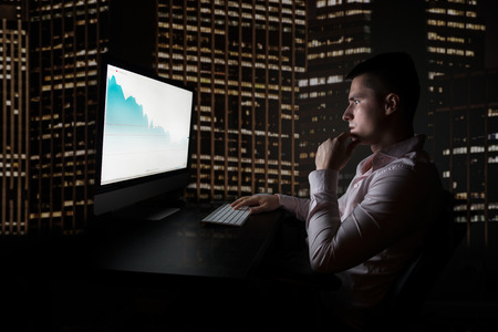 stock trader: Stock trader checking oil quotes on stock exchange market during night trading in the office in New York City Wall Street.