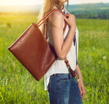 Beautiful girl holding brown leather hand bag outdoors on the sunny meadow at sunset time. Girl wearing fashionable white t-shirt and blue denim jeans.