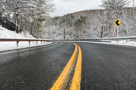 singn: beautiful winter landscape with highway road with turn and snow-covered trees. Clean mountain aspahlt winter road with yellow marking double lines and singn.  Stock Photo