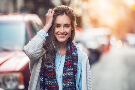 young adult woman: Happy young adult woman smiling with teeth smile outdoors and walking on city street at sunset time weating winter clothes and knitted scarf.