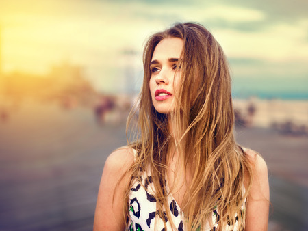 Beautiful girl enjoy the walk on the beach boardwalk at sunset time. Woman loking to the side outdoors. Banco de Imagens