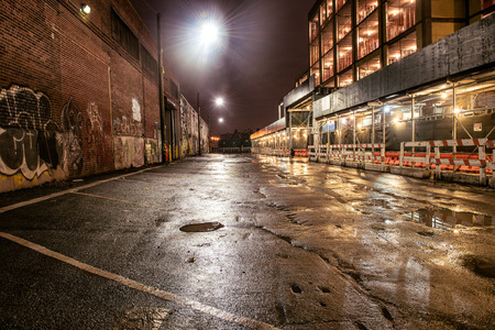 Asphalt street road in night city after the rain. Parking lot with graffiti on the brick walls.