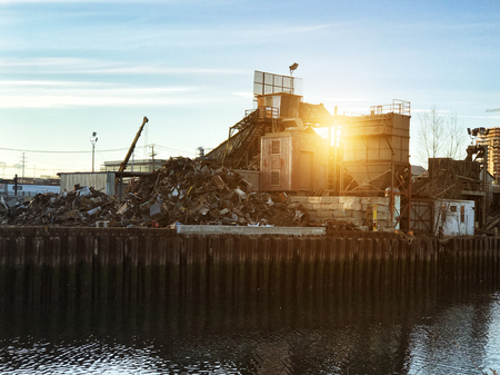 Car scrap metal dump recycling industrial factory at sunset time Stock Photo