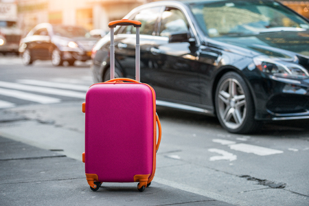 Luggage bag on the city street ready to pick by airport transfer taxy car.