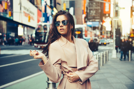 Fashionable girl walking on New York City street in Midtown wearing sunglasses and ping jacket. 免版税图像