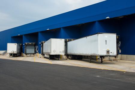 Stazione di consegna del servizio di trasporto. Grande magazzino di distribuzione con cancelli per carichi e camion