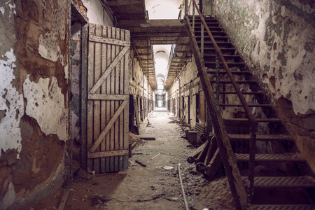 incarceration: Abandoned prison cell walkway with old rusty stairs, doors and peeling walls. Philadelphia Eastern State Penitentiary.