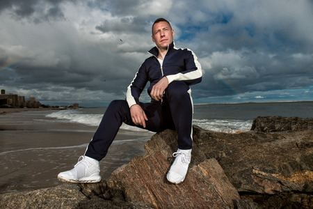 Adult man sitting on the rocks thinking and looking to the side wearing sport clothes and white sneakers.