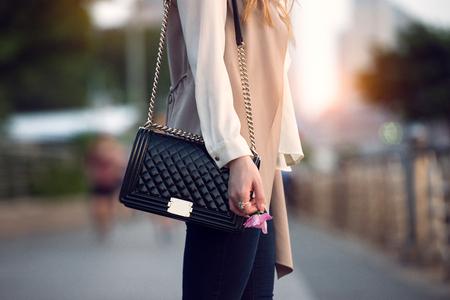 Nahaufnahme von stilvollen weiblichen schwarzen Ledertasche im Freien. Modische und luxuriöse Stil teure weibliche Tasche. Standard-Bild