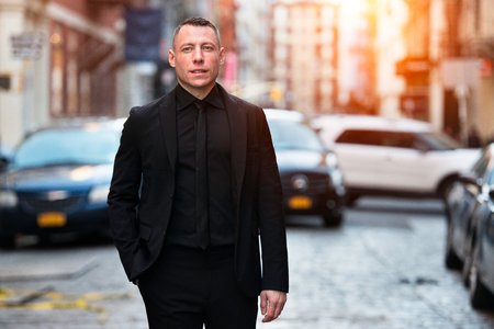 Adult successful businessman standing on city street wearing black suit. Stock Photo