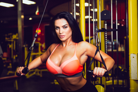 Sexy fitness model doing sport exercise in gym.