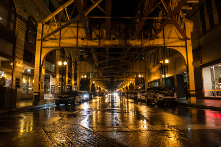 Night empty american city street with parked cars and subway in Chicago at rainy day Stock Photo
