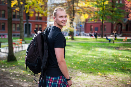 Happy smiling student man with backpack going to study in university campus