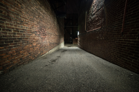 Scary empty dark alley with brick walls