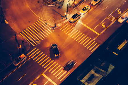Cars and people on road intersection with signal lights and crosswalks at night time in the city street 写真素材