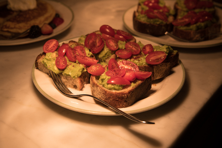 Avocado guacamole toasts with cherry potatoes on plates on a kitchen counter 免版税图像