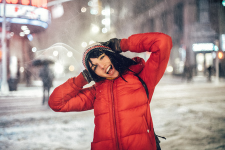 Happy exited woman having fun on city street of New York under the snow at winter time wearing hat and jacket. Stock Photo