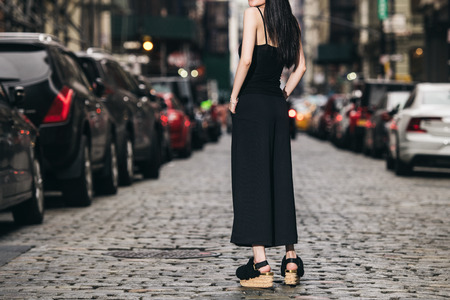 Female casual classic black style outfit with pants, top and shoes on city street
