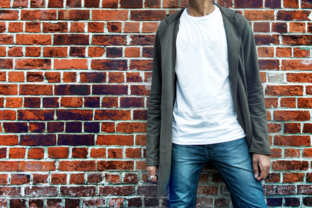 Fashionable man wearing modern stylish casual outfit with grey hoodie, blue jeans and white t-shirt posing near brick wall. Shopping concept.