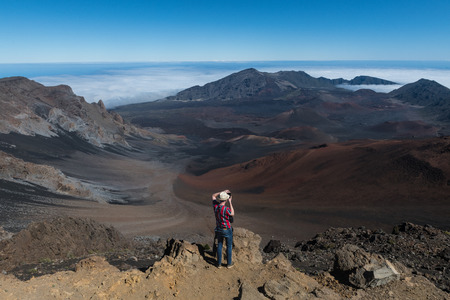 Hombre turista tomando fotos del valle de la montaña del volcán desde la cima en Big Island, Hawaii Foto de archivo
