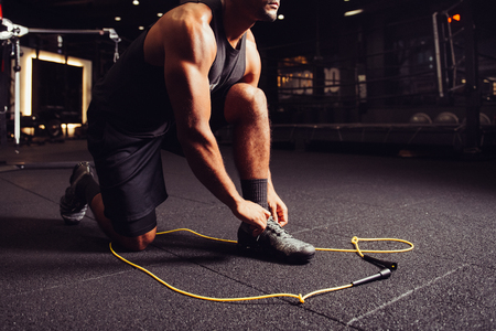 Man stretching up and getting ready to powerful workout on jump rope in boxing sport gym 免版税图像