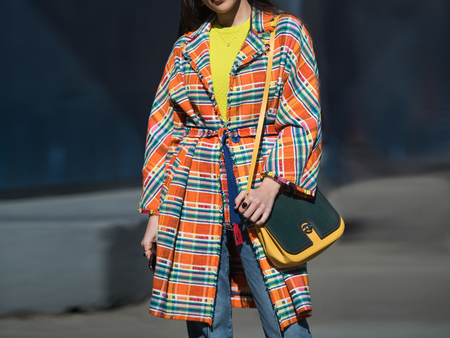 Colorful casual spring female look with checkered pattern jacket, blouse, jeans and leather bag.