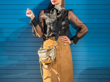 Fashionable stylish casual famale outfit with brown leather skirt, silver purse bag and black transparent shirt