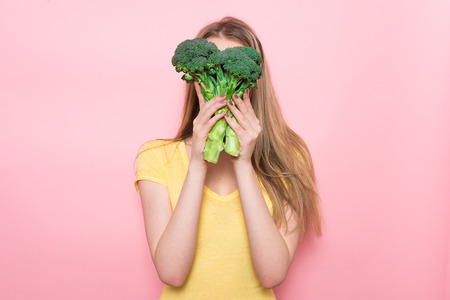 Woman have fun holding gluten-free organic green vegetable. Healthy nutrition food concept. 免版税图像