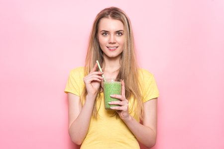 Beautiful young woman holds green smoothie with straw and smiling near pink wall