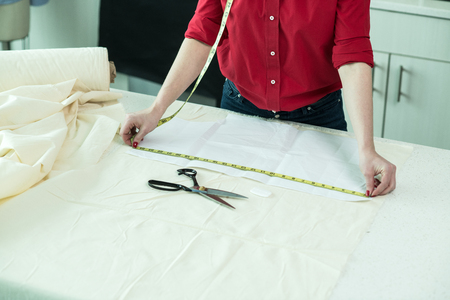 Tailor woman measuring a piece of textile cloth in the atelier 免版税图像