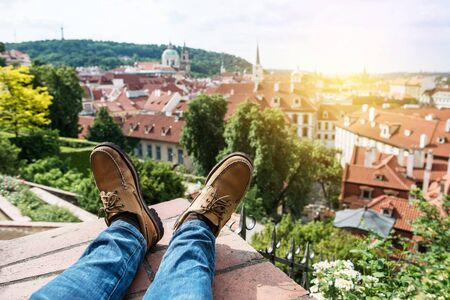 Man chilling on the rooftop sitting on the edge wearing leather shoes and enjoy the view of old town Prague, Czech Republic 免版税图像