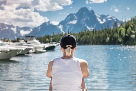 Woman travel and enjoy the nature view of a mountain lake with yachts and forest at summertime